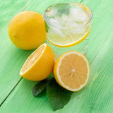 Lemonade in a glass, a lemon half, fresh leaves on the green table. A refreshing cold drink of water with ice, mint and slices of lemon, side view