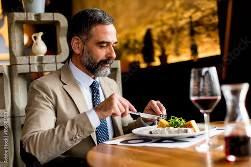Foto Murales Senior man eating lunch in restaurant