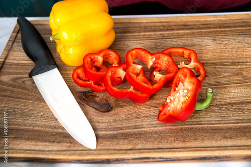 Pepper slices vegetable and ceramic knife on wooden cutting board - 186897197