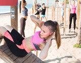 Focusing woman doing workout on beach in sunny morning - 186897930