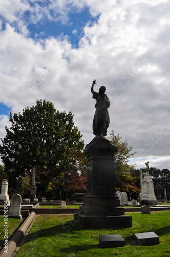 Silhouette of an Angel Statue Pointing Up to Heaven in a Cemetery - 186901934