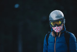 Snowboarder fashion portrait in frozen forest. Woman wearing sunglass mask and buff. Portrait of skier woman in the mountains