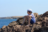 A boy in a striped T-shirt and cap sits on the rocks.