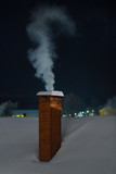 Chimney with white smoke during an cold winter evening