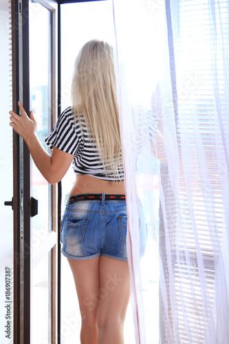 Blonde goes on terrace opening the door. Young woman in denim shorts, view from the back