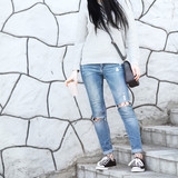 Fashionable woman sitting on stairs wearing ripped jeans with sneakers.