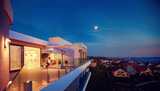 family relaxing on roof top patio with evening city view - 186929771