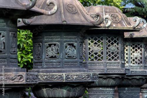 Poster Tokio Stone lanterns in Ueno Park, Taito ward, Tokyo, Japan. Line of japanese traditional lanterns or light towers at Ueno Toshogu Shrine.