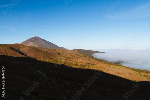 Deurstickers Canarische Eilanden Mountains above cloud inversion in desert landscape while sunrise