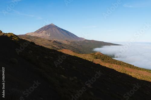 Deurstickers Canarische Eilanden Volcano above cloud inversion in desert landscape while sunrise