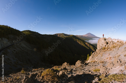 Deurstickers Canarische Eilanden Woman standing on the cliff with volcano in the background