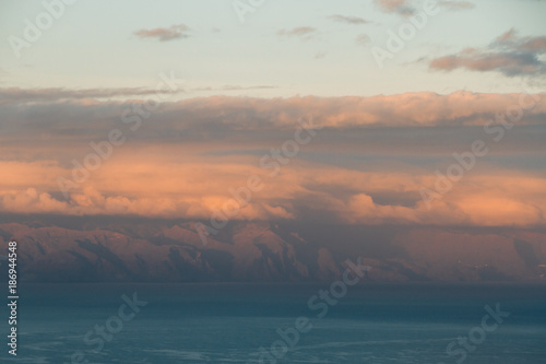 Deurstickers Canarische Eilanden Sunset light behind clouds above mountains and ocean