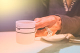 Female hands holding coffee cup over dark table - 186944759