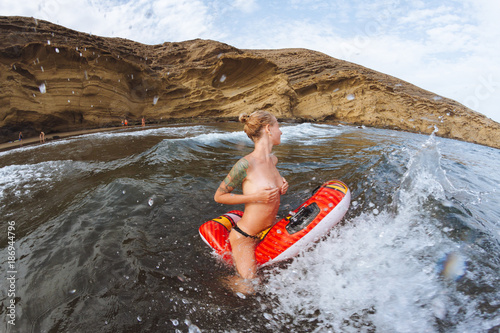 Deurstickers Canarische Eilanden Young topless girl in thongs on pool float in ocean waves