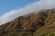 Houses on hillside of green mountain covered in fog
