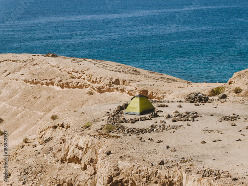 Tent on the top of the sand hill near water - 186945927