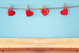 Valentines day background. hearts hanging in front of wooden background. product display backdrop.
