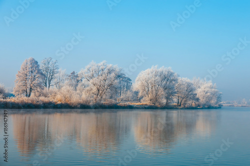 Foto op Plexiglas Blauw winter landscape with a river and trees covered with hoarfrost