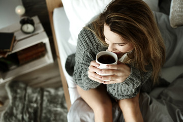 Attractive woman drinking coffee in bed .