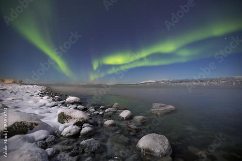 Fotobehang Noorderlicht Aurora borealis over a moonlit fjord in northern Norway