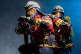 Feuerwehrtrupp bei der Brandbekämpfung mit PA, Flammen spiegeln sich in Atemschutzmasken