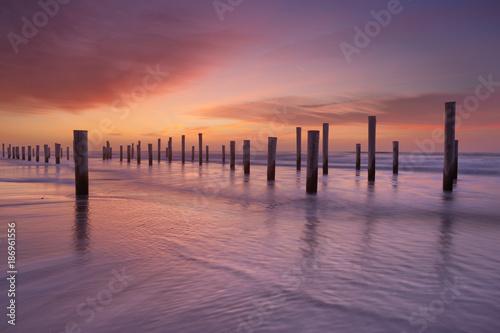 Aluminium Strand Wooden poles on the beach at sunset
