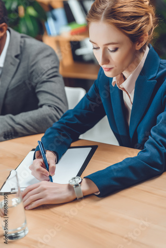 businesswoman writing on paper in folder on table at office space