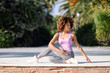 Black woman, afro hairstyle, doing yoga on promenade.