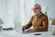 Senior confident man working on laptop
