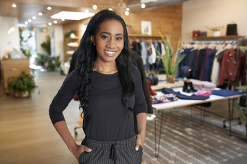 Young woman with hands in pockets smiling in a clothes shop