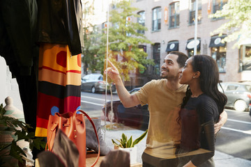 Smiling couple pointing at clothes in a shop window