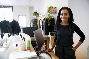 Female assistant smiling behind the counter in clothes store