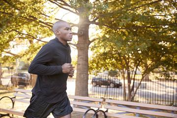 Young black man jogging in a Brooklyn park, close up