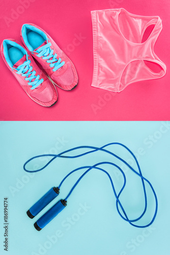 Sports equipment with shoes, skipping rope and sports top isolated on pink and blue - 186994774