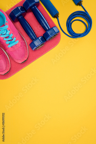 Foto Murales Sports equipment with shoes, dumbbells and skipping rope isolated on yellow