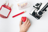 top view of hand holding red heart against vials with blood and microscope isolated on white background - 186996578