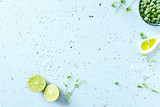 Symbolic food background with lime, olive oil, frozen peas and pea sprouts - 186996779
