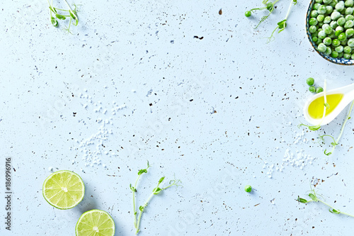Foto Murales Symbolic food background with lime, olive oil, frozen peas and pea sprouts