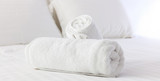 Hotel's bedroom. White fluffy, rolled towels, linen sheets and pillows on a bed. Close up view. - 186997941