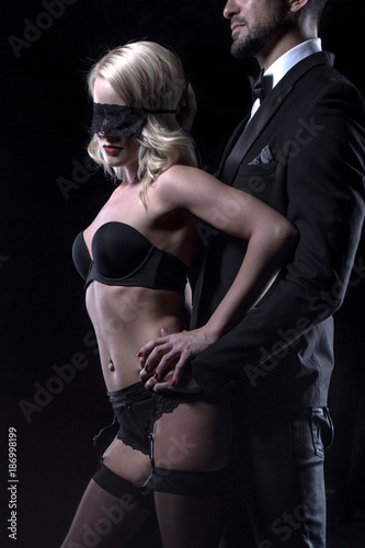 Stylish man touching sexy blonde lover in blindfold closeup
