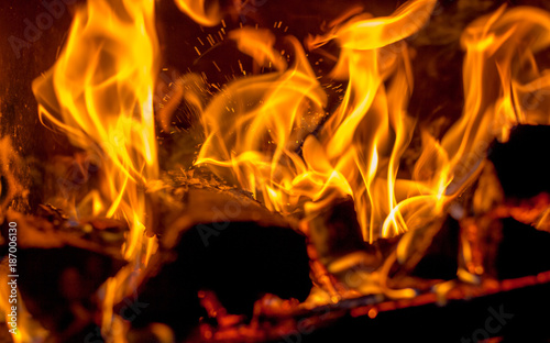 Foto op Aluminium Brandhout textuur In the fireplace a hot red fire burns brightly on a dark background_