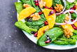 Salad with spinach leaves and orange, pomegranate and nuts.Light healthy vitamin salad bowl text space.Diet and detox concept.