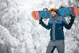 Sportsman holding ski board and return from skiing terrain