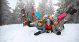 Happy group of skiers lying on snow