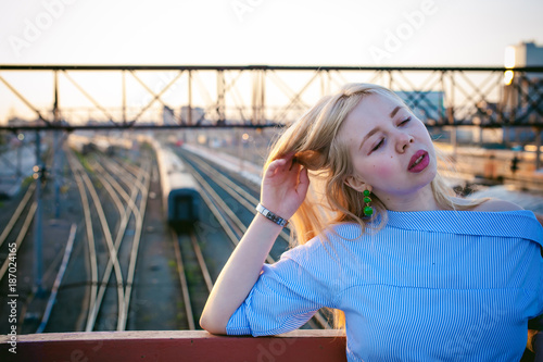 portrait of a cute young blond woman in a summer day against the background of a railway station