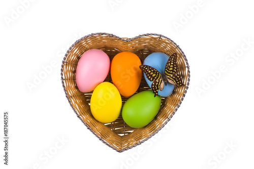 Easter eggs in a basket on white isolated background