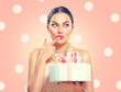 Funny joyful beauty model girl holding big beautiful party or birthday cake over pink background and tasting it