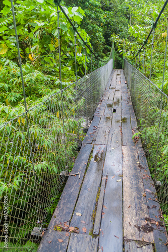 Suspension bridge at the hiking trail Sendero Los Quetzales in National Park Volcan Baru during rainy season, Panama. - 187063928
