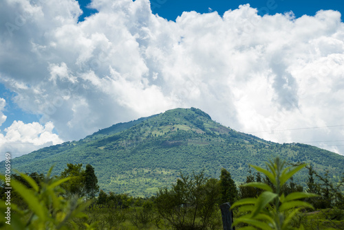 Fotobehang Wit Summer landscape with mountains, cloudy sky, green grass and trees in Guatemala.
