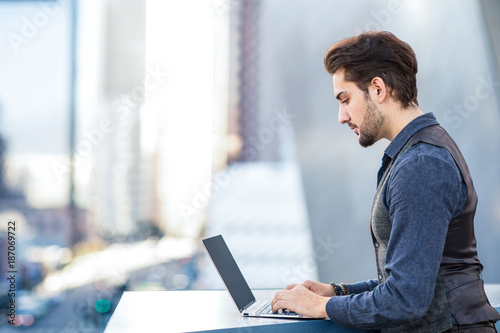 Young romantic man working on his laptop in the city